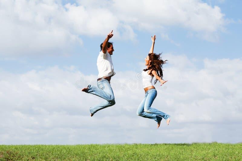 Springende frohe Paare lizenzfreie stockbilder