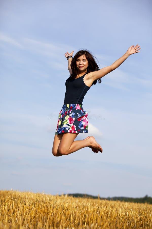 Springende gelukkige donkerbruine tiener stock foto's