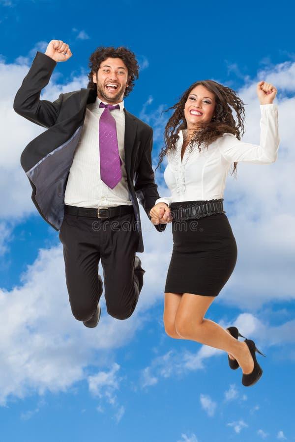 Springende Geschäftspaare stockfoto