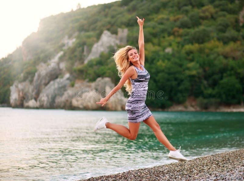 Springende glückliche Frau auf Seeküste auf Hintergrund von Bergen stockfoto