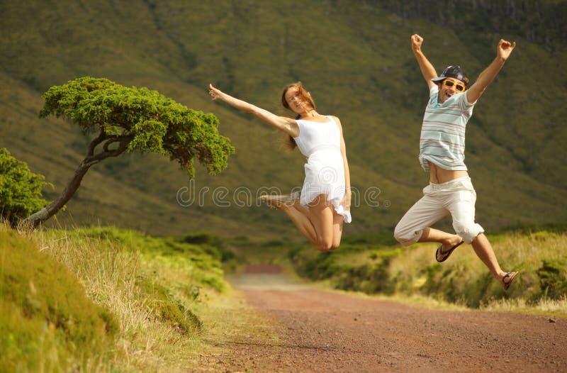 Springende glückliche lächelnde junge Paare im honneymoon auf Azoren-Insel lizenzfreie stockfotos