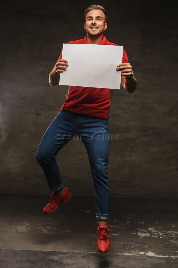 Springende jonge mens die in jeans en rode t-shirt wit blad o houden stock afbeeldingen