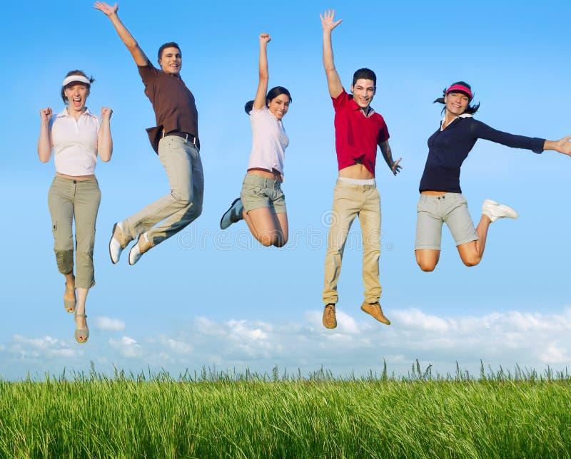 Springende jonge mensen gelukkige groep in weide royalty-vrije stock fotografie
