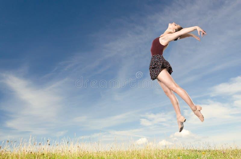 Springende junge Frau stockfotos