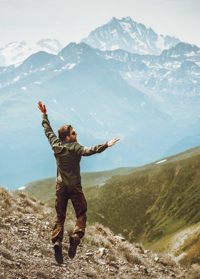 Springende Levitation des glücklichen Mannes in der Berglebensstil-Reise emotional stockfotos