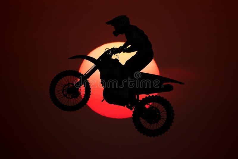 Springende motocross met grote zonachtergrond stock foto