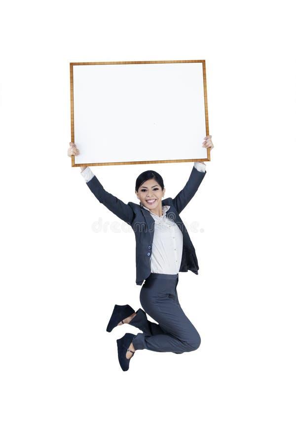 Springende opgewekte onderneemster die lege raad houden stock afbeeldingen