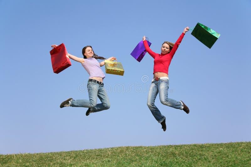 Springende Paarmädchen mit Beuteln stockfotos