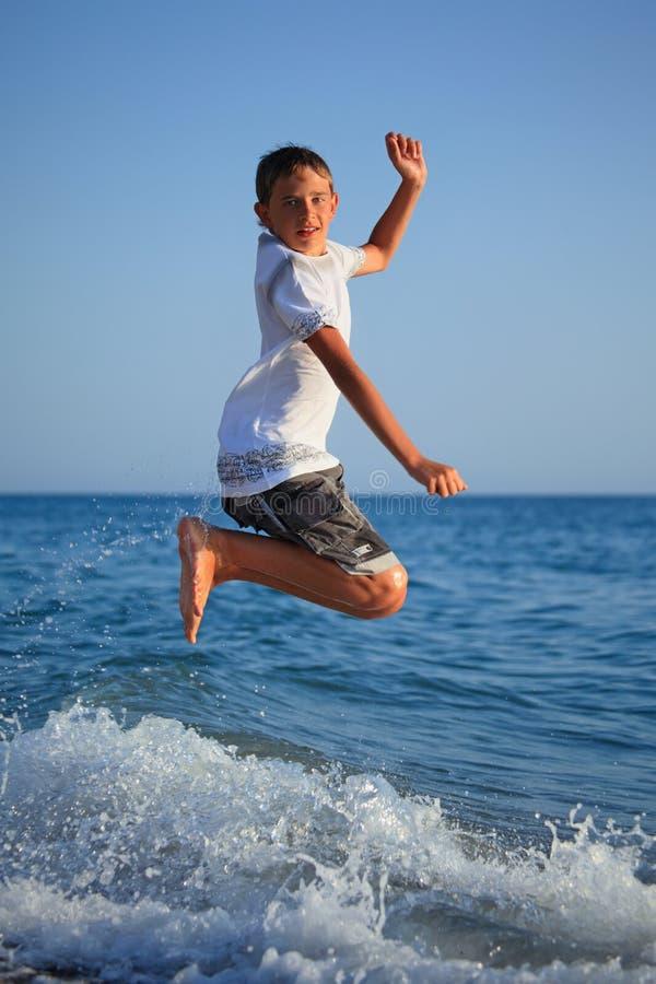 Springende tienerjongen op zeekust stock afbeelding