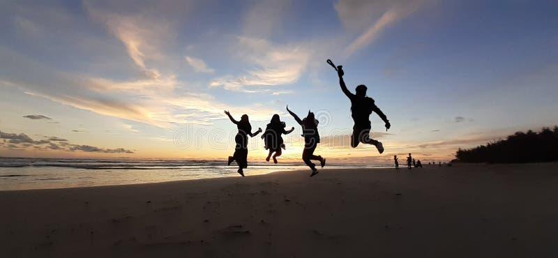 Springende tieners op het zonsondergangstrand stock foto