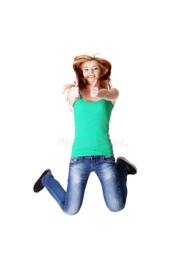 Springende tienerstudent die o.k. gebaar toont