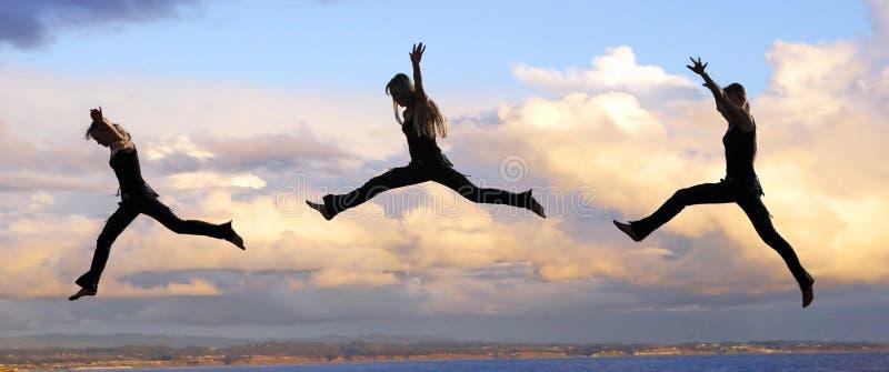 Springende vrouw bij zonsondergang stock fotografie