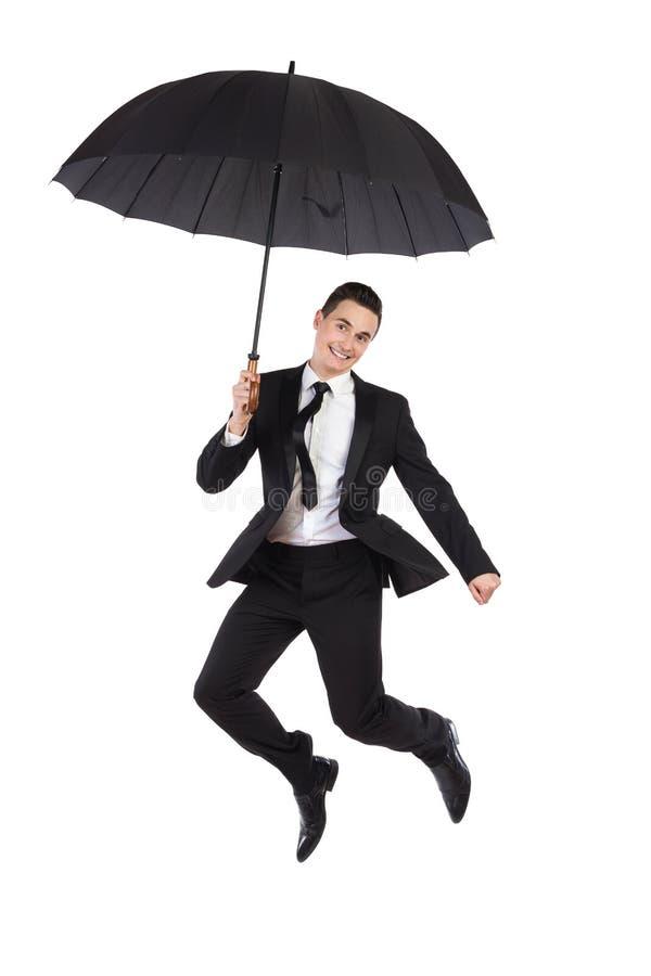 Springender Geschäftsmann mit einem Regenschirm lizenzfreie stockfotos