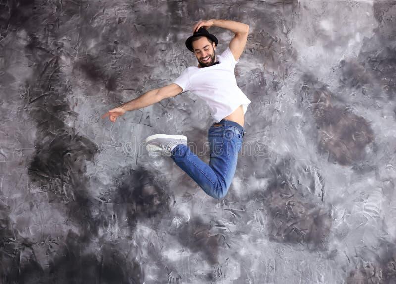 Springender männlicher Tänzer gegen Schmutzwand lizenzfreie stockbilder