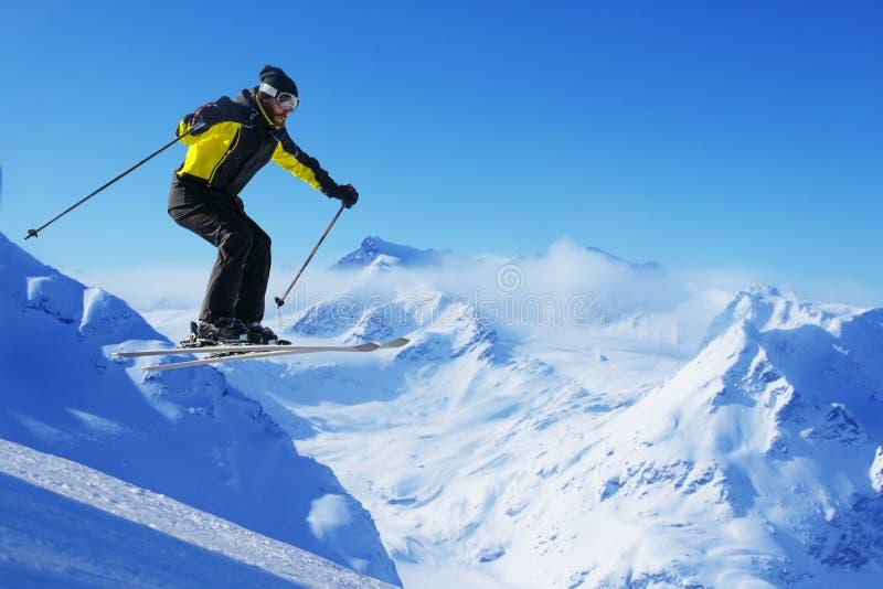 Springender Skifahrer an den Bergen lizenzfreies stockfoto