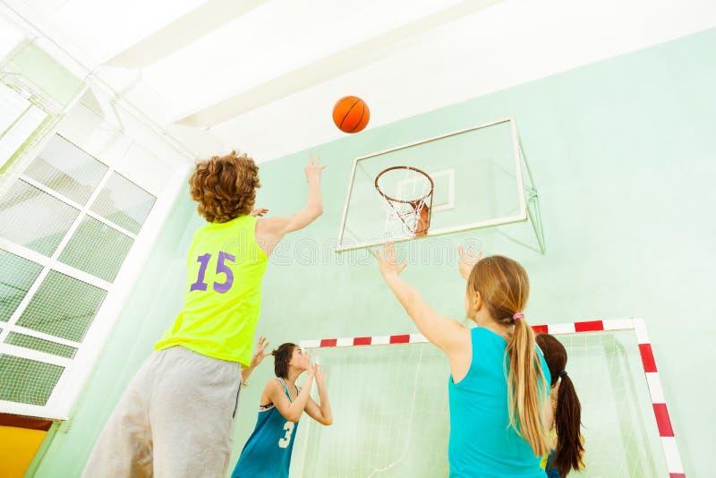 Springender und werfender Ball des Jungen in den Korb lizenzfreie stockfotos