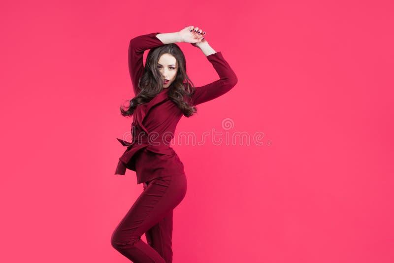 Springendes bezauberndes Mädchen Attraktiver junger Brunette gekleidet in Burgunder-Farbe, rosa Farbhintergrund stockfoto