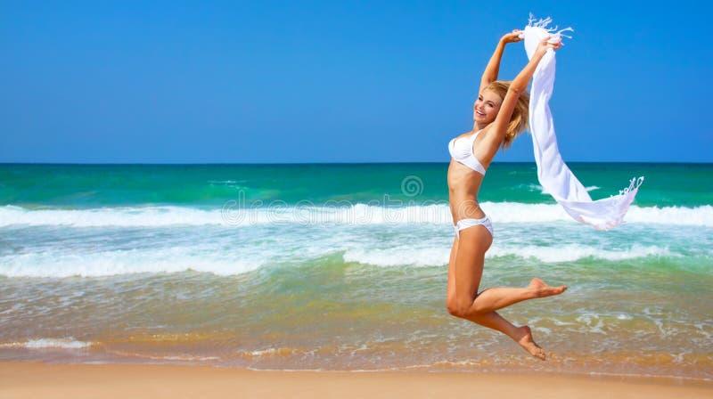 Springendes glückliches Mädchen auf dem Strand lizenzfreie stockfotografie
