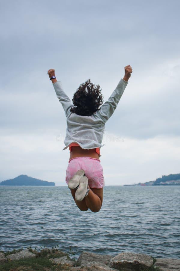 Springendes Hoch des jungen Mädchens, welches das Meer gegenüberstellt stockbild