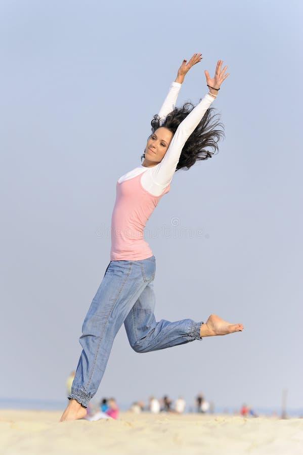Springendes junges Mädchen auf Strand lizenzfreie stockbilder