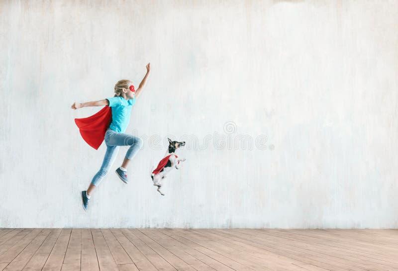 Springendes kleines Kind mit einem Hund stockfoto