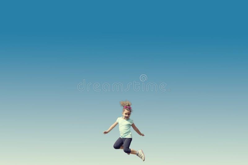 Springendes kleines Mädchen stockfoto