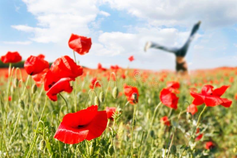 Springendes Mädchen auf dem Mohnblumegebiet lizenzfreies stockbild