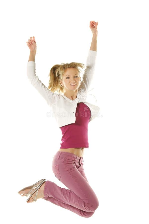 Springendes Mädchen in den rosafarbenen Jeans lizenzfreies stockbild