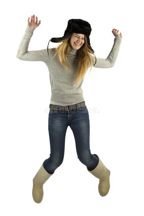 Springendes Mädchen in earflapped Hut lizenzfreie stockfotografie