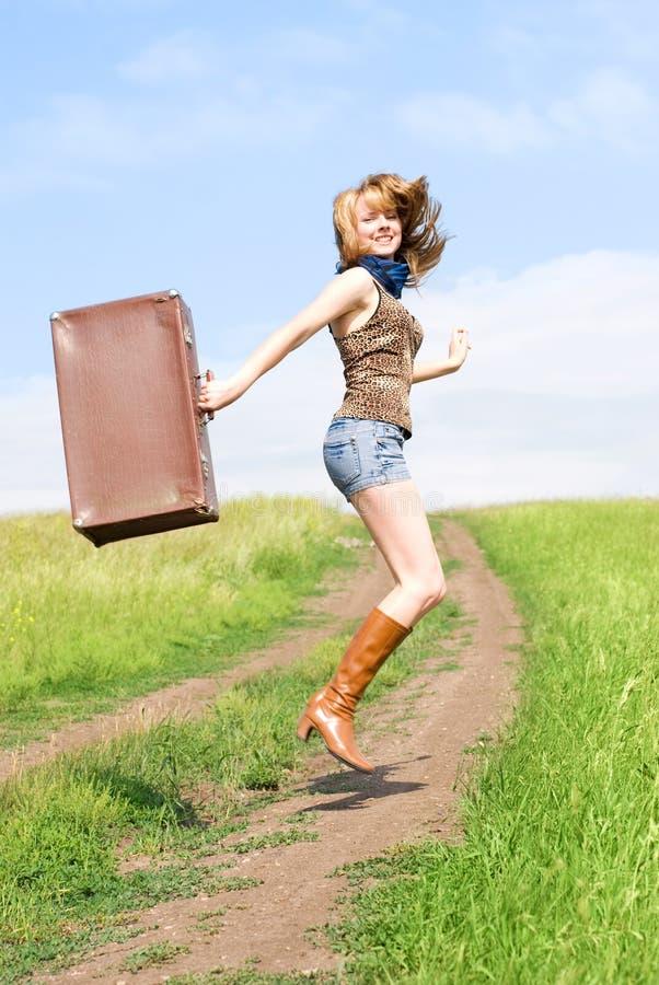 Springendes Mädchen mit einem Koffer stockfoto