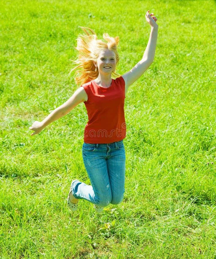 Springendes red-haired jugendlich Mädchen stockbilder