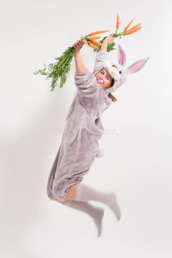 Springendes schönes Ostern-Kaninchenmädchen mit Karotten stockfotografie