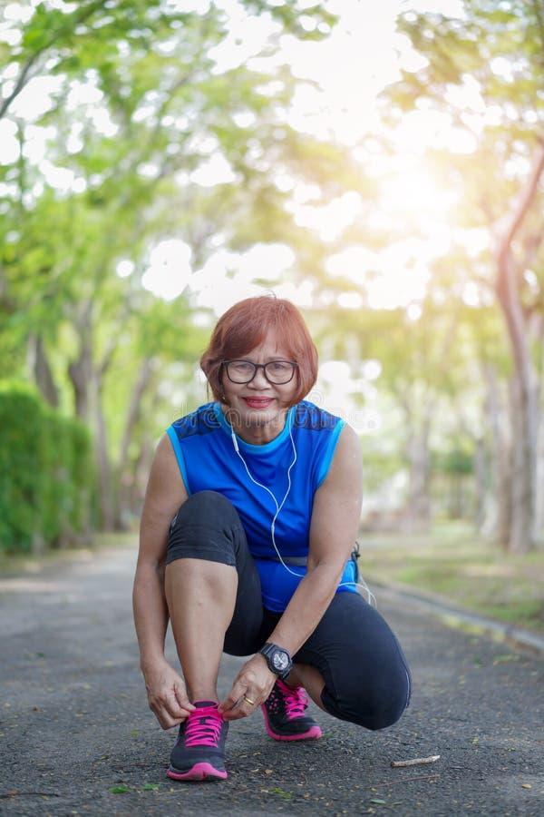 Springskor - den höga asiatiska kvinnan som joggar parkerar igenom fotografering för bildbyråer