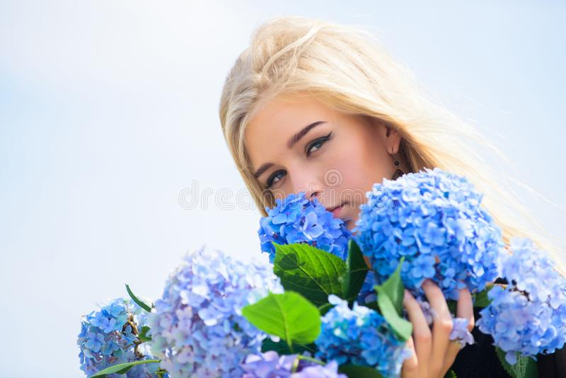 Springtime bloom. Girl tender blonde hold hydrangea flowers bouquet. Natural beauty concept. Skin care and beauty. Treatment. Gentle flower for delicate woman royalty free stock photography