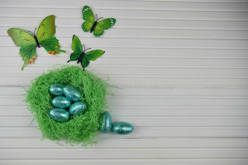Springtime Easter decoration with handmade green color nest filled with blue shiny foil eggs and butterfly shape decorations royalty free stock images