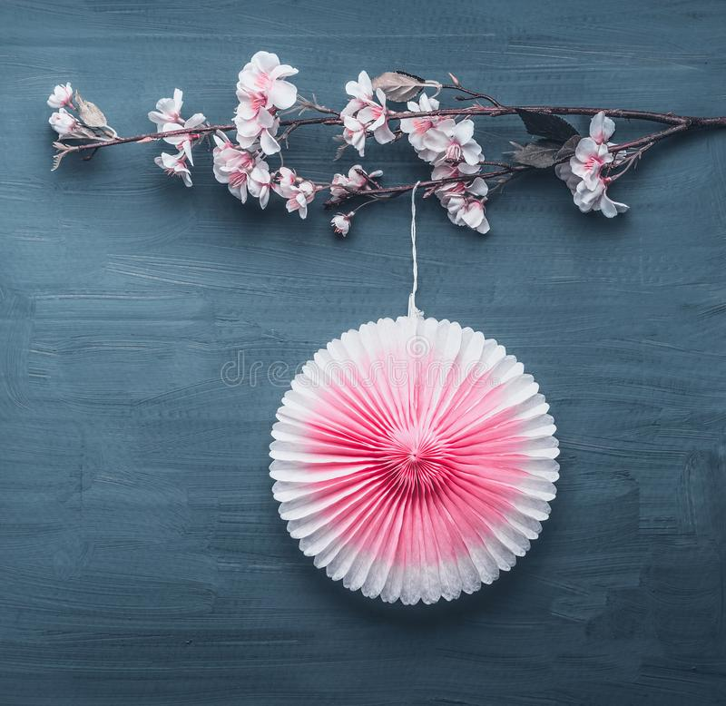 Springtime decoration with artificial spring blossom twig and pink party paper fan stock photography