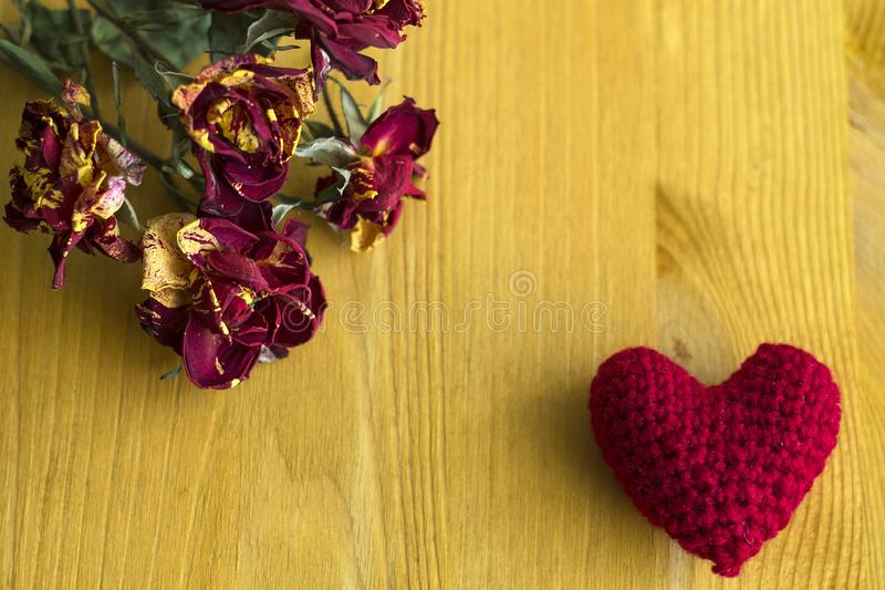 Springtime. Dried red roses on a wooden yellow background with a red knitted heart royalty free stock photography