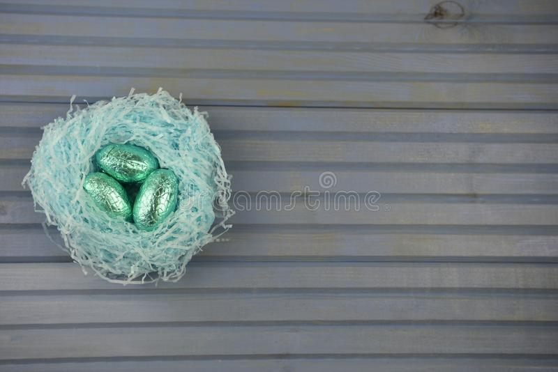 Springtime Easter decoration with handmade blue nest filled with shiny chocolate eggs on rustic wood background stock image