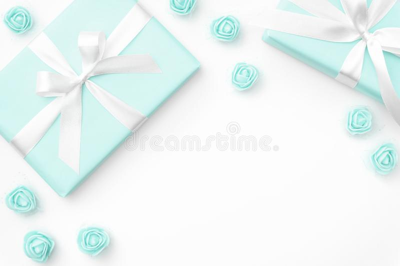 Springtime layout turquoise gift box and rose flowers top view for 8 March Women day copy space isolated on white background. royalty free stock photography