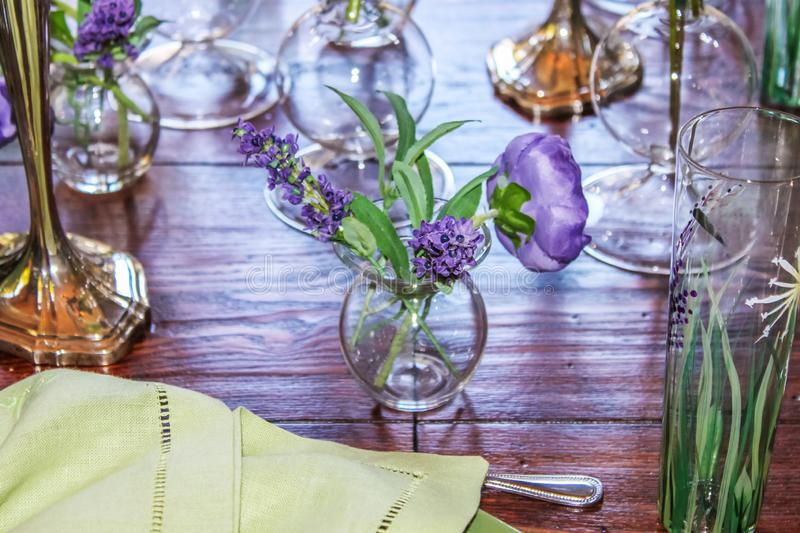 Springtime - Pale lime linen napkin and a variety of vases sit on a wooden table in shades of purple and green - close-up and stock photography