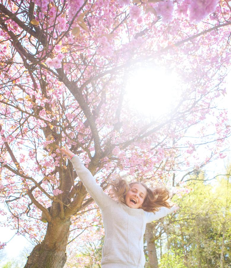 Springtime young girl jumping before cherry tree stock photo