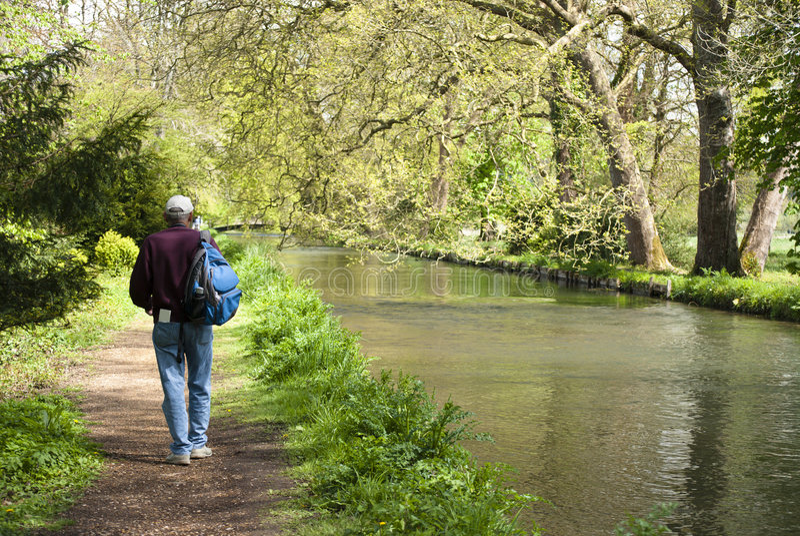 Springtime river walk. Senior man hiking along a beautiful river in Springtime stock photo