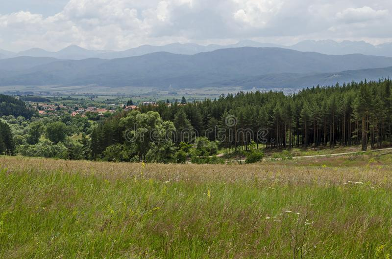 Springtime scene with glade, forest and residential district of bulgarian village Alino in Plana mountain near Rila  and Verila. Mountains, Bulgaria royalty free stock photo