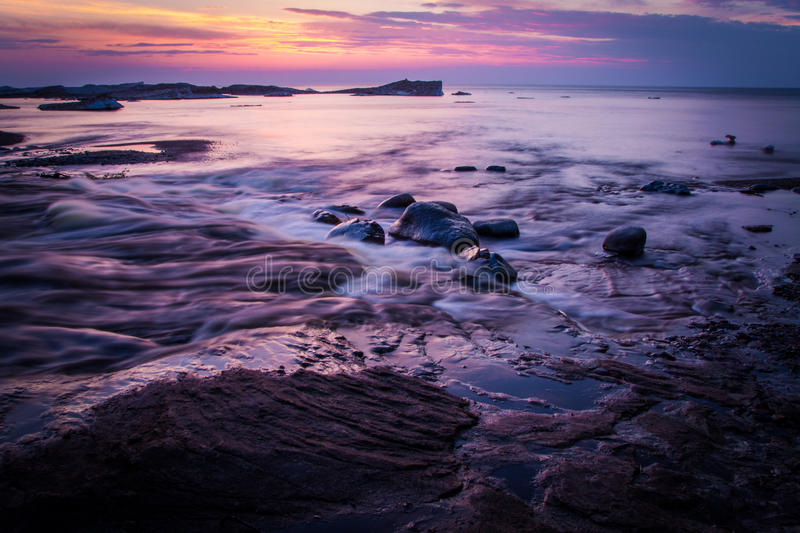 Springtime On The Shores Of Lake Superior. The sunsets on the shores of Lake Superior while icebergs float on the horizon. Pictured Rocks National Lakeshore royalty free stock images