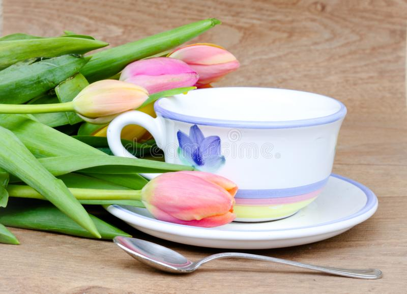 Springtime tea. Springtime background with a nicely decorated cup of tea and fresh tulips on a wooden background stock photo