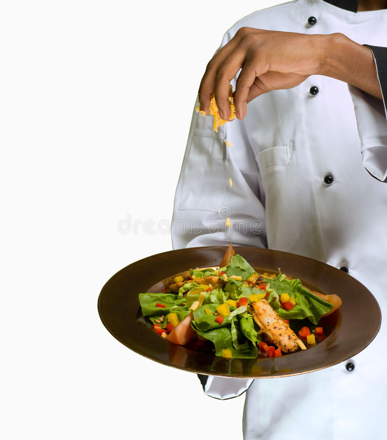 Sprinking Käse des Chefs auf Salat lizenzfreie stockbilder