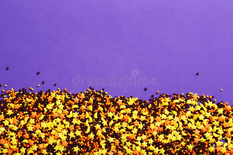 Sprinkle dots and stars. Colorful sprinkle dots and stars on purple background royalty free stock photo