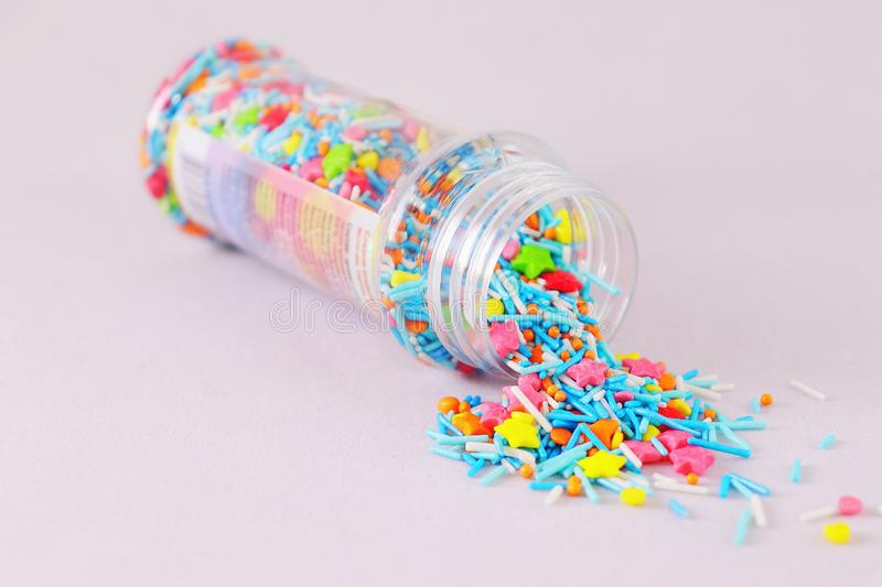 Sprinkle for Easter cakes scattered from a can on a white surface. Topping in the form of colored stars, balls, sticks royalty free stock photos