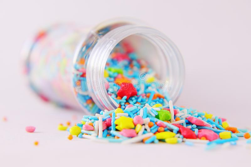 Sprinkle for Easter cakes scattered from a can on a white surface. Topping in the form of colored stars, balls, sticks stock image