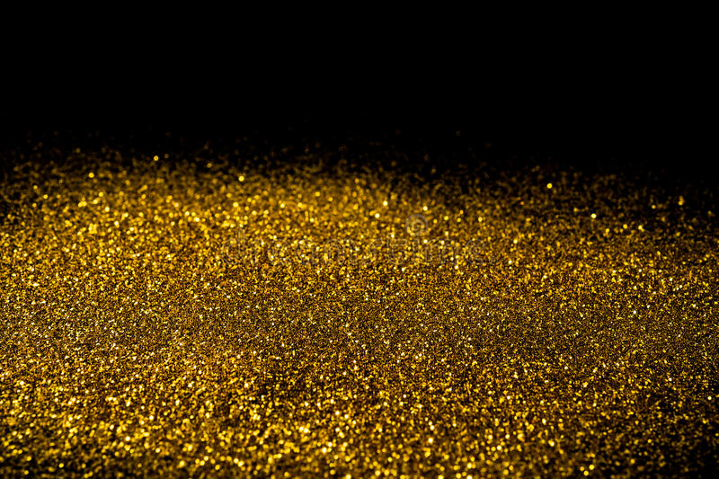 Sprinkle gold dust on a black background royalty free stock image